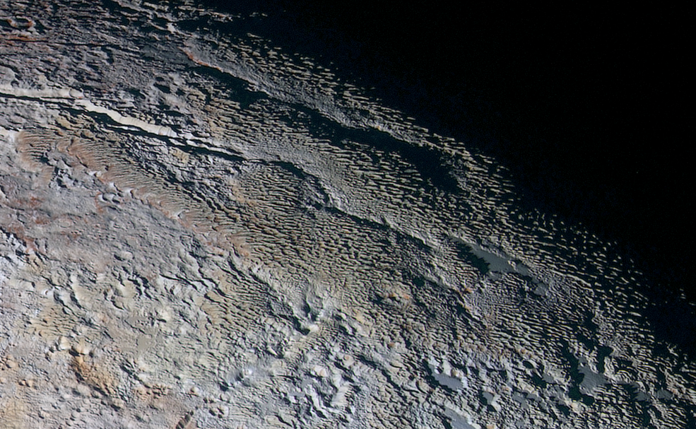 In this extended color image of Pluto taken by NASA's New Horizons spacecraft, rounded and bizarrely textured mountains, informally named the Tartarus Dorsa, rise up along Pluto's day-night terminator and show intricate but puzzling patterns of blue-gray ridges and reddish material in between. This view, roughly 330 miles (530 kilometers) across, combines blue, red and infrared images taken by the Ralph/Multispectral Visual Imaging Camera (MVIC) on July 14, 2015, and resolves details and colors on scales as small as 0.8 miles (1.3 kilometers). Image Credit: NASA/JHUAPL/SWRI