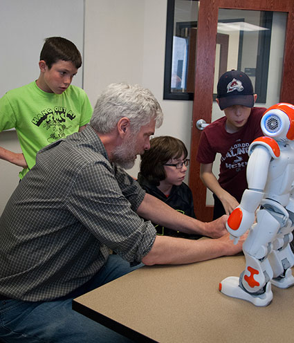 George Sellman, Adams State assistant professor of computer science, helps students program a humanoid robot during the spring 2015 STEM Saturdays. Image Credit: Adams State University