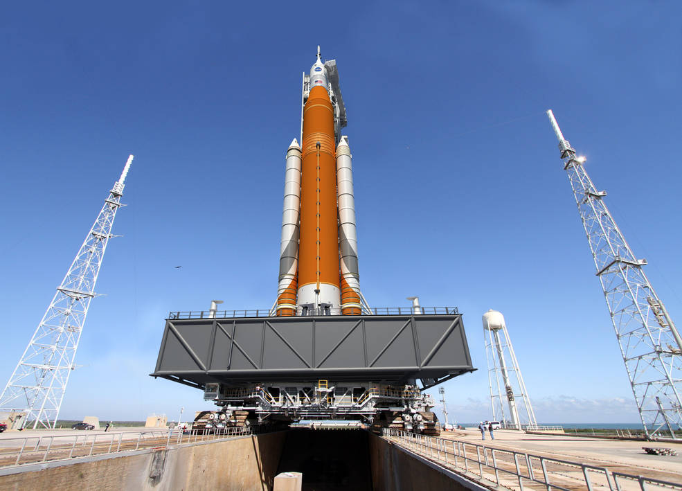 Artist concept of the Block I configuration of NASA's Space Launch System (SLS). The SLS Program has completed its critical design review, and the program has concluded that the core stage of the rocket will remain orange along with the Launch Vehicle Stage Adapter, which is the natural color of the insulation that will cover those elements. Image Credit: NASA