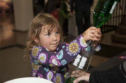 A budding scientist participates in an experiment at a previous Super Science Saturday. Image Credit: UCAR/Carlye Calvin