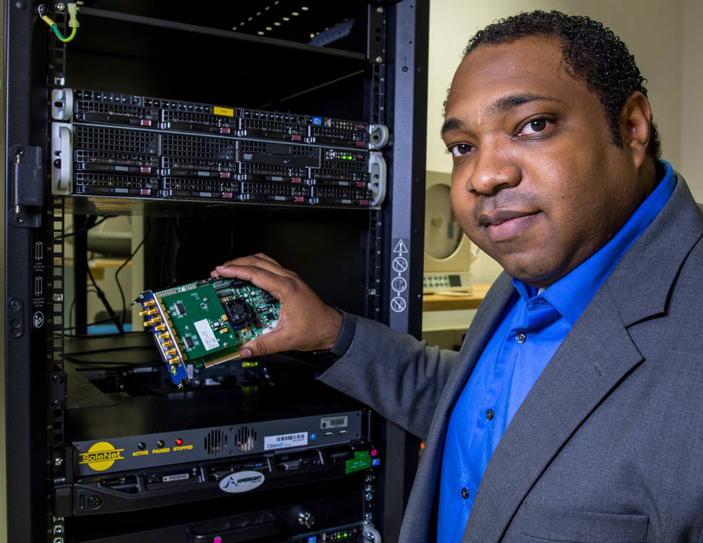 Philip Baldwin holds the custom-designed high-speed interface card that enables data transfer from Antarctica to White Sands, New Mexico, at about 300 Mbps. The electronics rack in the background is similar to the one inside the radome housing the new equipment. Image Credit: NASA/W. Hrybyk