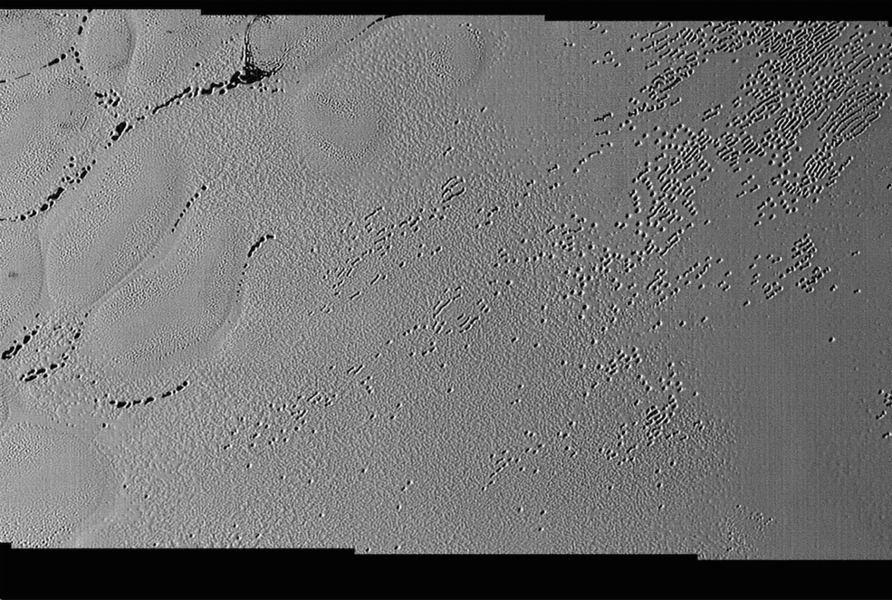 This image was taken by the Long Range Reconnaissance Imager (LORRI) on NASA's New Horizons spacecraft shortly before closest approach to Pluto on July 14, 2015; it resolves details as small as 270 yards (250 meters). The scene shown is about 130 miles (210 kilometers) across. The sun illuminates the scene from the left, and north is to the upper left. Image Credit: NASA/JHUAPL/SwRI