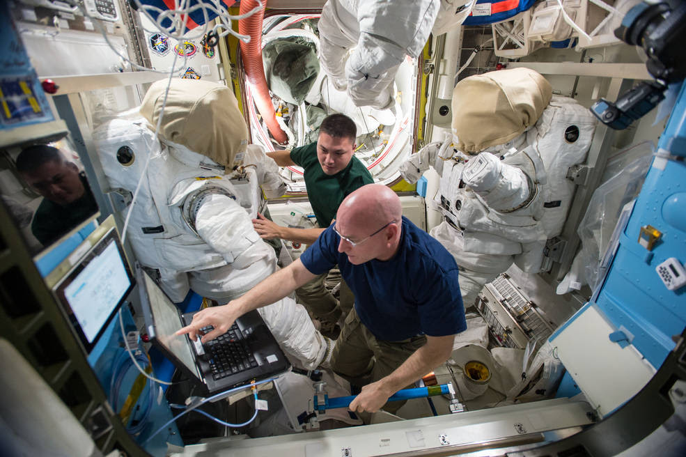 Expedition 45 commander Scott Kelly and flight engineer Kjell Lindgren prepare their extravehicular mobility unit spacesuits and tools in the Quest airlock. Kelly and Lindgren will use the spacesuits for two upcoming spacewalks outside the International Space Station on Oct. 28 and Nov. 6, 2015. Image Credit: NASA