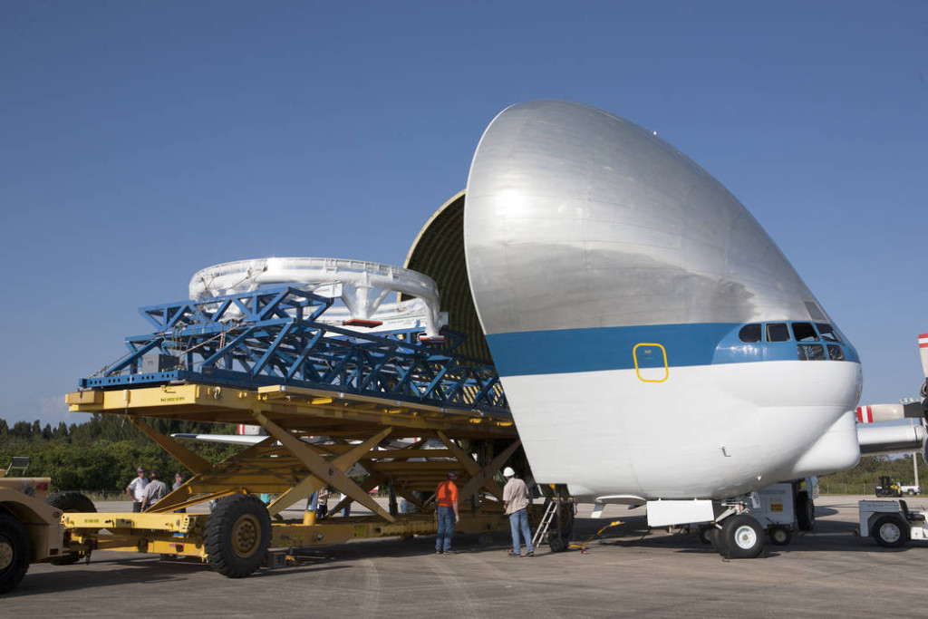 The Orion spacecraft service module stacking assembly interface ring and stack holding stand are secured on a special transportation platform and are being loaded into NASA's Super Guppy aircraft at the Shuttle Landing Facility at NASA's Kennedy Space Center in Florida. Image Credit: NASA/Kim Shiflett