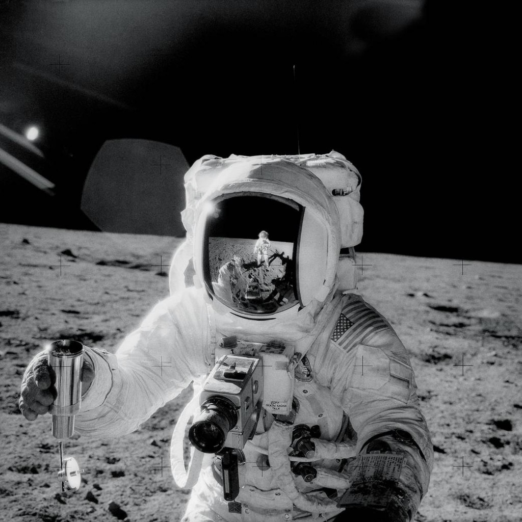 Apollo 12 astronaut Alan Bean holds a special environmental sample container filled with lunar soil collected during his sojourn on the lunar surface. A Hasselblad camera is mounted on the chest of his spacesuit. Pete Conrad, who took this image, is reflected in Bean's helmet visor, Nov. 20, 1969. Image Credit: NASA