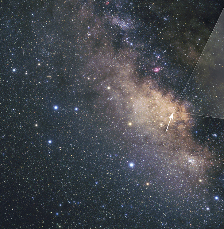 Ground-based view of the Milky Way's central bulge, seen in the direction of the constellation Sagittarius. Giant dust clouds block most of the starlight coming from the galactic center. Hubble however, peered through a region (marked by the arrow) called the Sagittarius Window, which offers a keyhole view into the galaxy's hub. Image Credit: A. Fujii