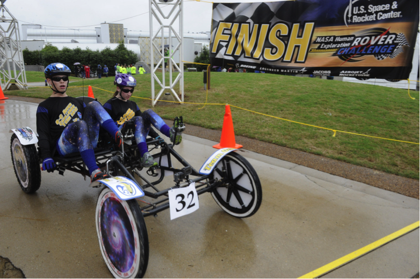 The Greenfield Central High School Rover Team from Greenfield, Indiana, crosses the finish line during the 2015 Human Exploration Rover Challenge held near NASA's Marshall Space Flight Center. Image Credit: NASA/MSFC/Emmett Given
