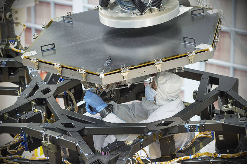An engineer at NASA's Goddard Space Flight Center worked to install the first flight mirror onto the telescope structure at NASA's Goddard Space Flight Center in Greenbelt, Maryland. Image Credit: NASA/Chris Gunn