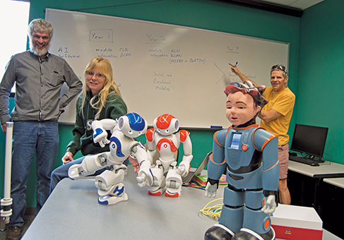 Faculty members (from left) George Sellman, Dr. Comfort Cover, and Dr. Matt Ikle demonstrate their robots' capabilities and describe goals for the Summer Research Internship Program in Artificial Intelligence and Social and Emotional Robotics. Image Credit: ASU