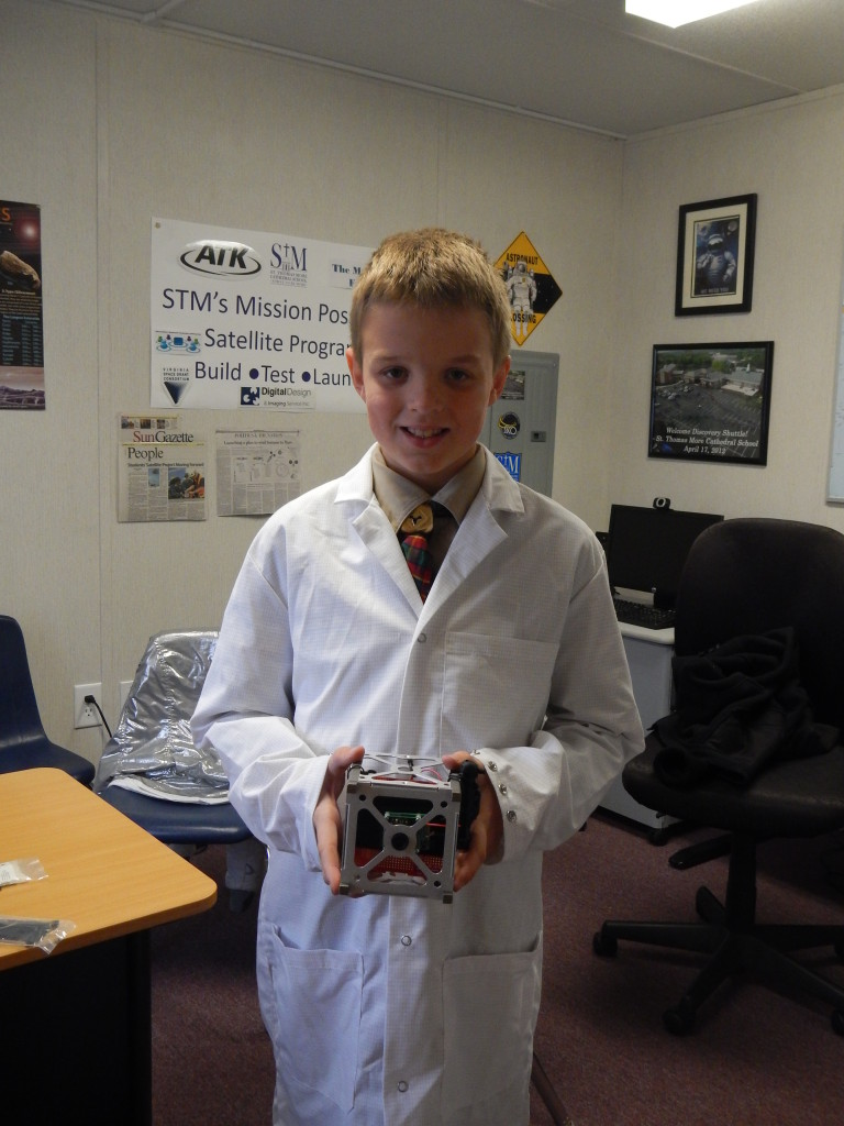 A student from St. Thomas More Cathedral School holds the STMSat-1 CubeSat. Image Credit: St. Thomas More Cathedral School