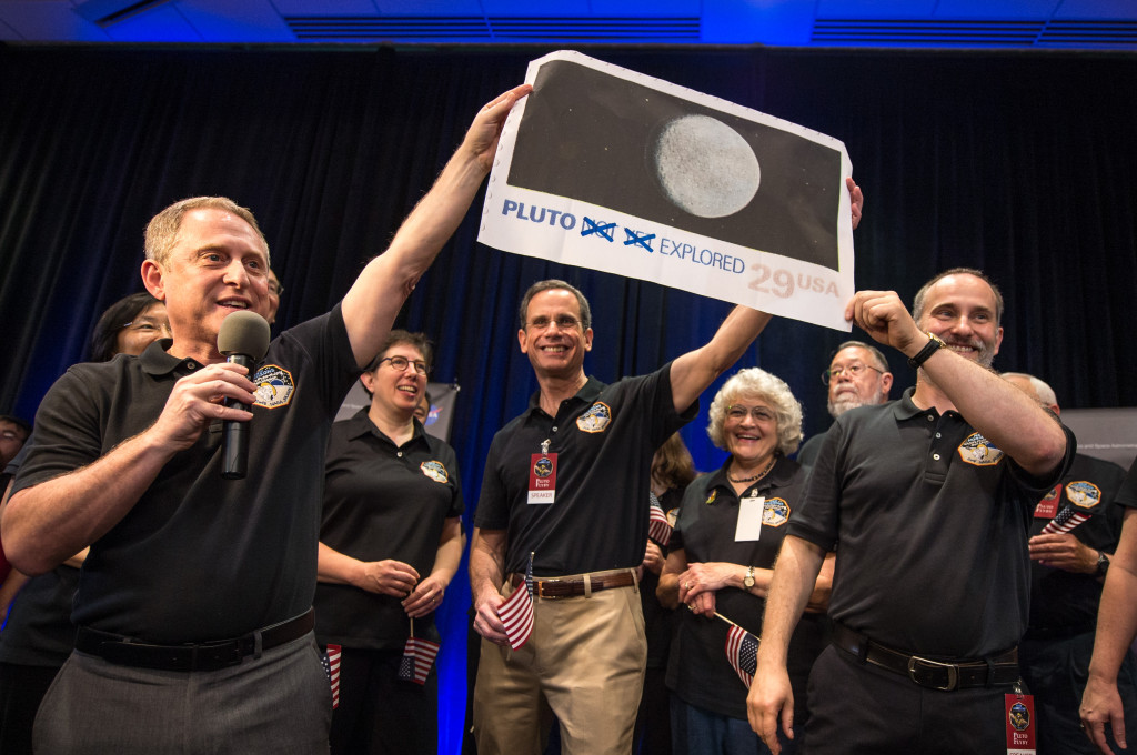 Pluto Explored. (left to right): New Horizons Principal Investigator Alan Stern of Southwest Research Institute (SwRI), Boulder, Colorado; New Horizons' Deputy Project Scientist Leslie Young, SwRI; Johns Hopkins University Applied Physics Laboratory (APL) Director Ralph Semmel; Annette Tombaugh, daughter of Clyde Tombaugh, who discovered Pluto in 1930; and New Horizons Co-Investigator Will Grundy, Lowell Observatory, Flagstaff, Arizona hold a print of the 1991 Pluto stamp –with their suggested update – on July 14 at APL in Laurel, Maryland. Image Credit: NASA/Bill Ingalls
