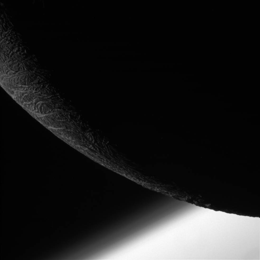 NASA's Cassini spacecraft paused during its final close flyby of Enceladus to focus on the icy moon's craggy, dimly lit limb, with the planet Saturn beyond. Image Credit: NASA/JPL-Caltech/Space Science Institute