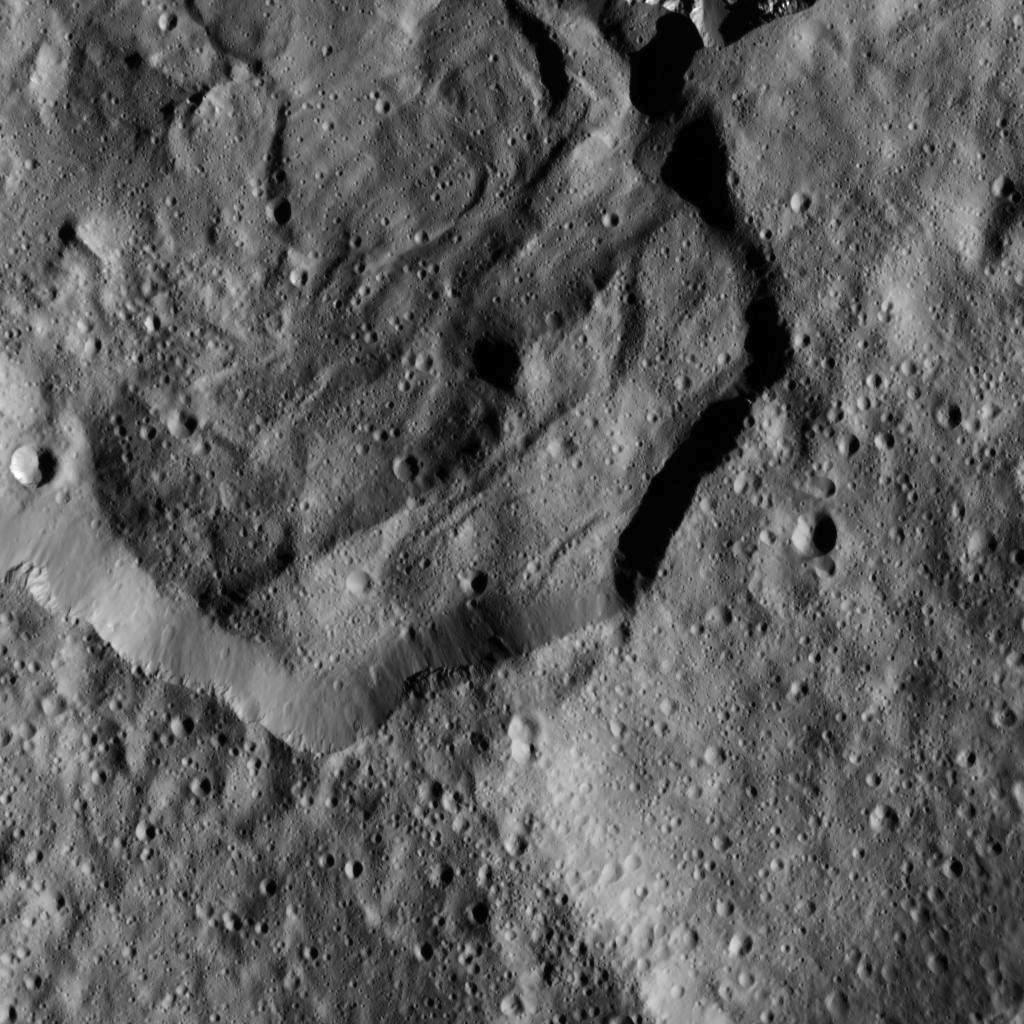 This image from NASA's Dawn spacecraft shows part of Messor Crater (25 miles or 40 kilometers, wide), located at northern mid-latitudes on Ceres. The scene shows an older crater in which a large lobe-shaped flow partly covers the northern (top) part of the crater floor. The flow is a mass of material ejected when a younger crater formed just north of the rim. Image Credit: NASA/JPL-Caltech/UCLA/MPS/DLR/IDA