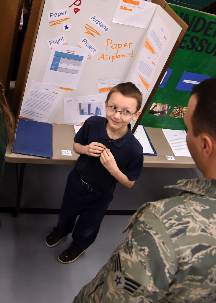 Devin Andrews, a sixth grade student, explains dihedral to Senior Airman Michael Fruit, 2nd Space Operations Squadron, during a science fair Friday, Feb. 19, 2016, at Colorado Springs Charter Academy in Colorado Springs, Colorado. Andrews used paper airplanes to test his hypothesis and concluded how dihedral, or aircrafts' wings' angle, directly impacts flight quality. Image Credit: USAF/Staff Sgt. Debbie Lockhart