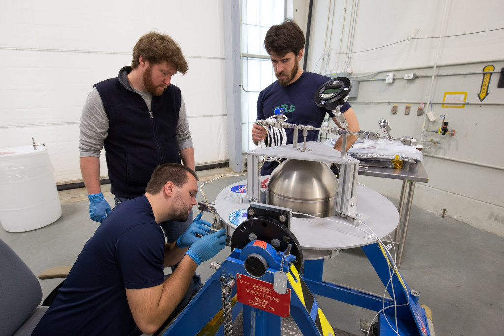A Goddard team, led by engineer Henry Mulkey (middle), prepares a tank containing a Swedish-developed green propellant before its simulated loading at the Wallops Flight Facility late last year. Kyle Bentley (squatting) and Joe Miller (standing to the right of Mulkey) assisted in the demonstration. Image Credit: NASA/C. Perry