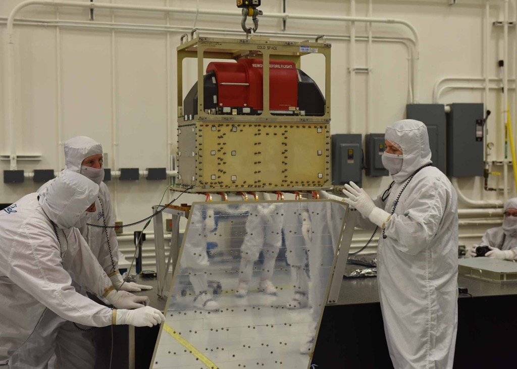 Ball Aerospace technicians lower the ATMS instrument onto the JPSS-1 spacecraft. Image Credit: Ball Aerospace & Technologies Corp.