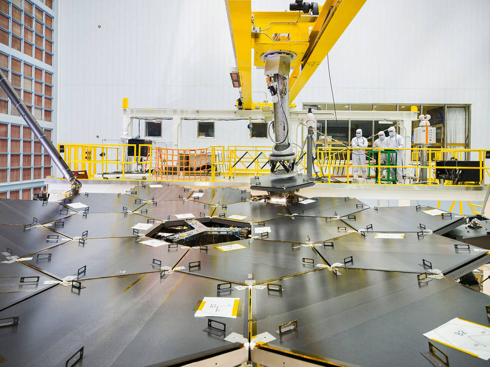 Inside a massive clean room at NASA's Goddard Space Flight Center in Greenbelt, Maryland the James Webb Space Telescope team used a robotic am to install the last of the telescope's 18 mirrors onto the telescope structure. Image Credit: NASA/Chris Gunn
