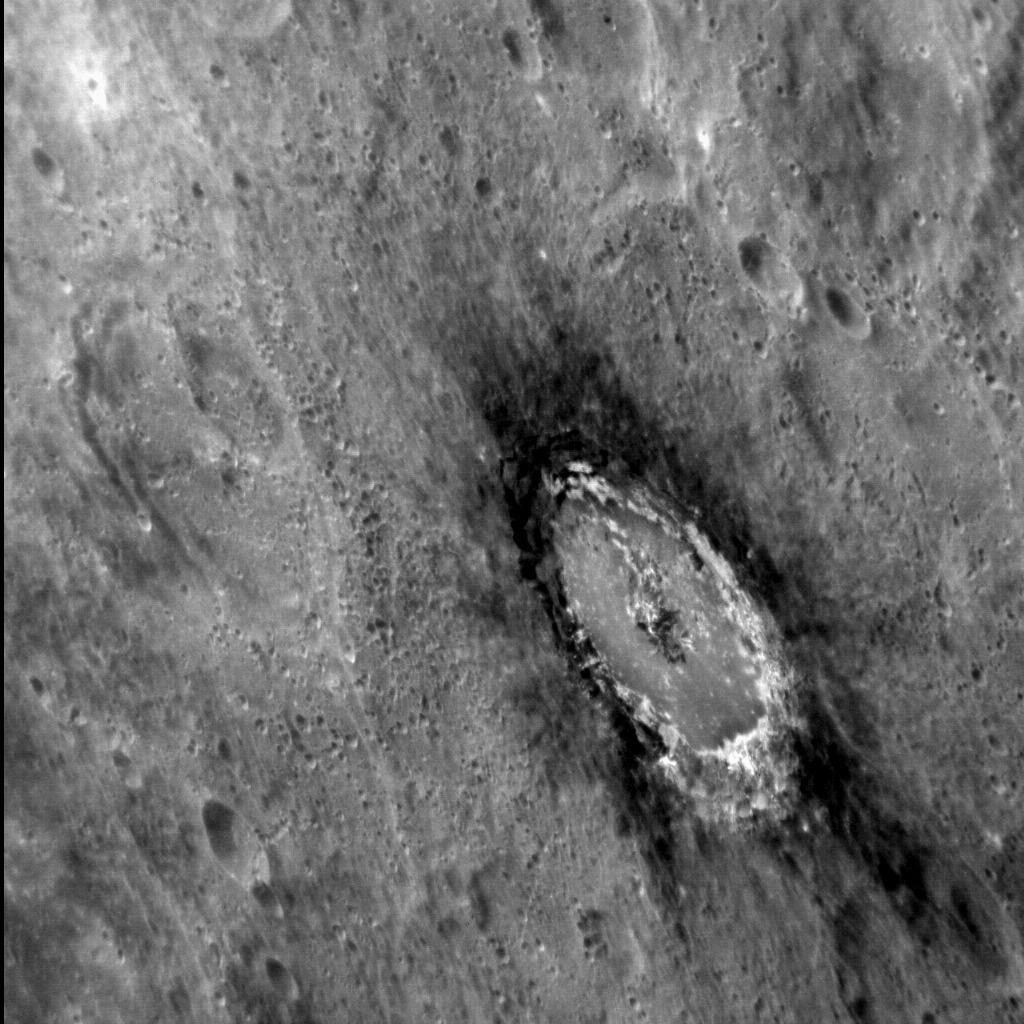 "This striking, oblique image of Basho shows the distinctive dark halo that encircles the crater. The halo is composed of ""Low Reflectance Material,"" which was excavated from depth when the crater was formed. Basho is also renowned for its bright ray craters, which render the crater easily visible even from very far away. Image Credit: NASA/Johns Hopkins University Applied Physics Laboratory/Carnegie Institution of Washington"
