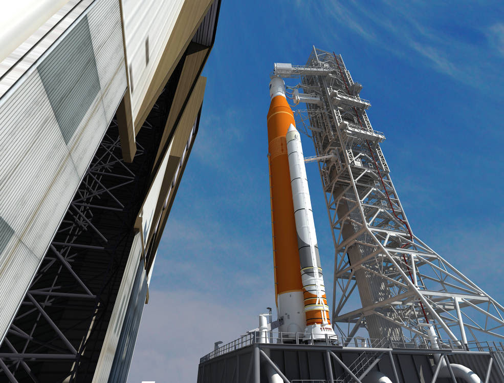 This artist concept depicts the Space Launch System rocket rolling out of the Vehicle Assembly Building at NASA's Kennedy Space Center. SLS will be the most powerful rocket ever built and will launch the agency's Orion spacecraft into a new era of exploration to destinations beyond low-Earth orbit. Image Credit: NASA/Marshall Space Flight Center