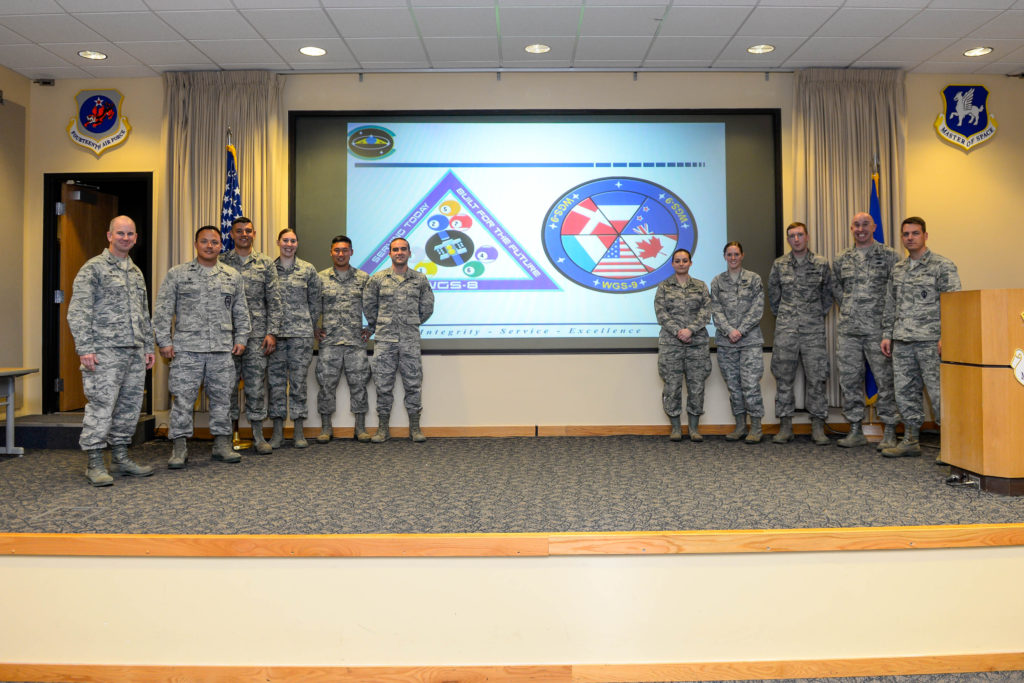 Col. Dennis Bythewood (left), 50th Operations Group commander, and Lt. Col. Chris Todd (second from left), 3rd Space Operations Squadron commander, present the eight Airmen selected to be part of the Launch and Early Orbit Teams for Wideband Global SATCOM-8 and 9 during a ceremony at Schriever Air Force Base, Colorado, Thursday, April 21, 2016. The Airmen endured a competitive selection process, which includes knowledge-based tests, problem solving scenarios and interviews. Image Credit: U.S. Air Force/Christopher DeWitt