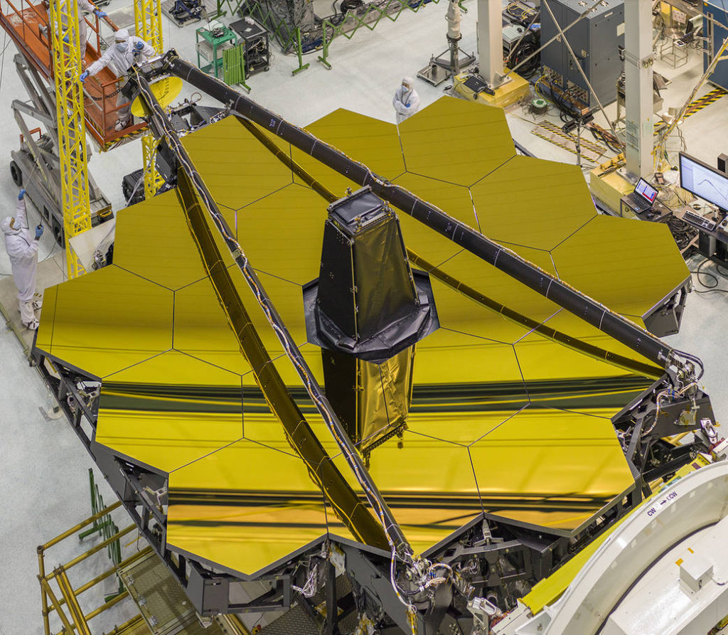 Inside the clean room at NASA's Goddard Space Flight Center, the golden James Webb Space Telescope is viewed from overhead with its secondary mirror booms stowed. This is the position the secondary mirror will be in during launch.  Image Credit: NASA/Chris Gunn