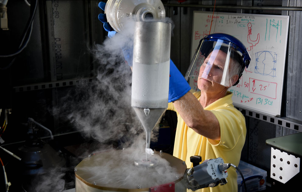 Rick Rudy adds liquid nitrogen to cool the infrared detectors in the VNIRIS instrument.Image Credit: Elisa Haber