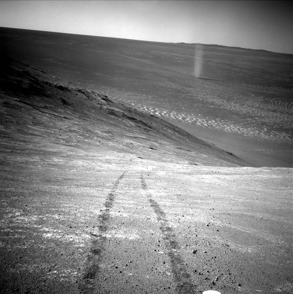"From its perch high on a ridge, NASA's Mars Exploration Rover Opportunity recorded this image of a Martian dust devil twisting through the valley below. The view looks back at the rover's tracks leading up the north-facing slope of ""Knudsen Ridge,"" which forms part of the southern edge of ""Marathon Valley."" Image Credit: NASA/JPL-Caltech"
