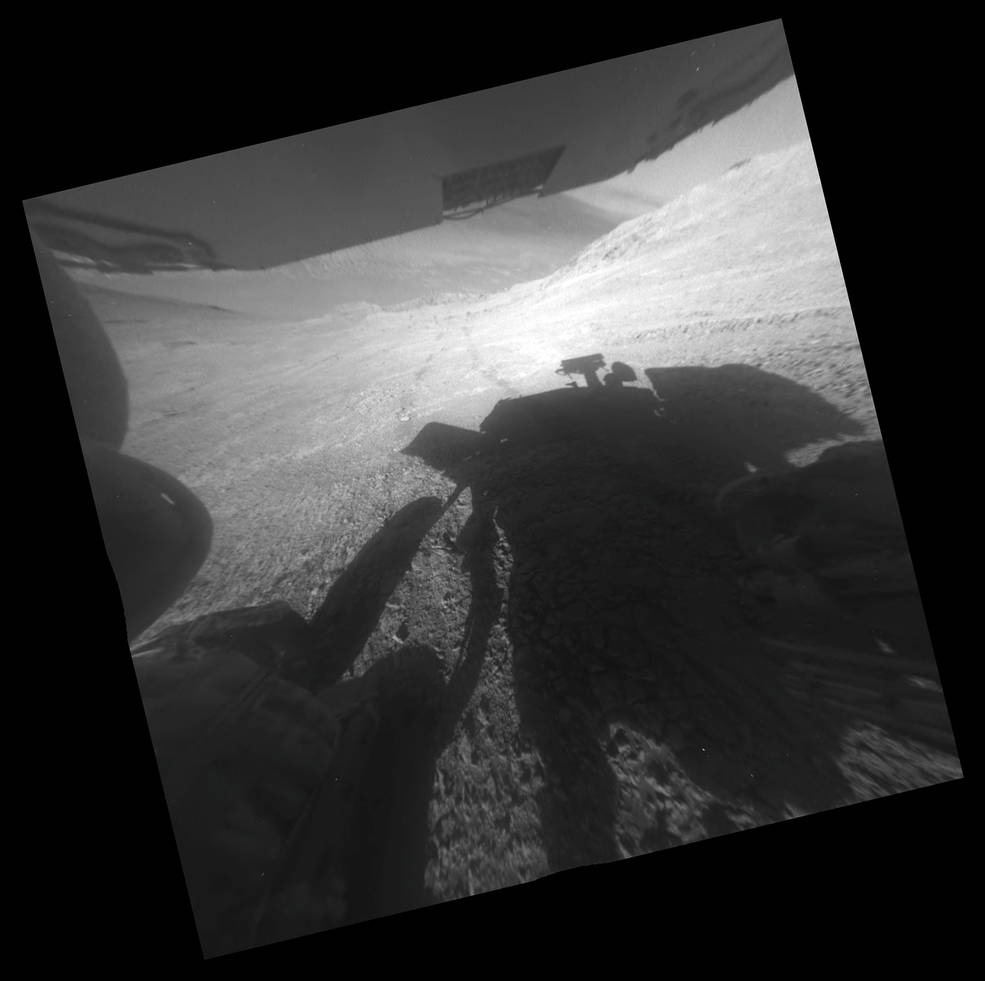 "A shadow and tracks of NASA's Mars rover Opportunity appear in this March 22, 2016, image, which has been rotated 13.5 degrees to adjust for the tilt of the rover. The hillside descends to the left into ""Marathon Valley."" The floor of Endeavour Crater is seen beneath the underside of a solar panel. Image Credit: NASA/JPL-Caltech"