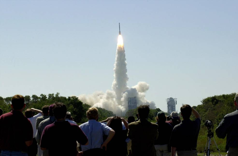 At 11:02 a.m. EDT on April 7, 2001, crowds watch a Boeing Delta II rocket lift off from Cape Canaveral Air Force Station, Florida, carrying NASA's 2001 Mars Odyssey spacecraft into space on its seven-month journey to Mars. Image Credit: NASA