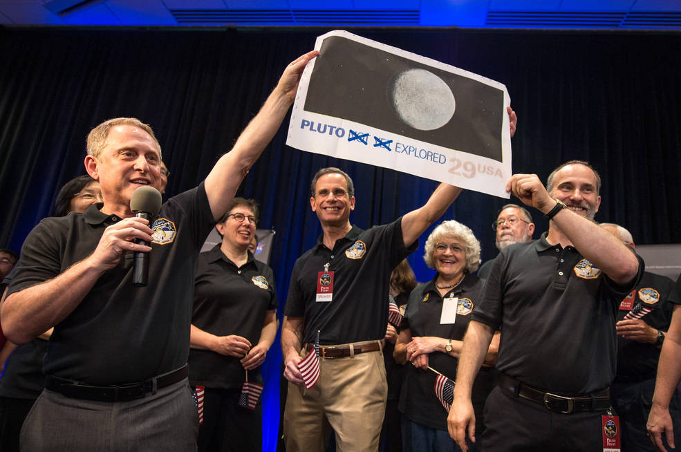 New Horizons Principal Investigator Alan Stern of Southwest Research Institute (SwRI), Boulder, CO., left, Johns Hopkins University Applied Physics Laboratory (APL) Director Ralph Semmel, center, and New Horizons Co-Investigator Will Grundy Lowell Observatory hold a print of an U.S. stamp with their suggested update since the New Horizons spacecraft has explored Pluto,  Tuesday, July 14, 2015 at the Johns Hopkins University Applied Physics Laboratory (APL) in Laurel, Maryland. Image Credit: NASA/Bill Ingalls