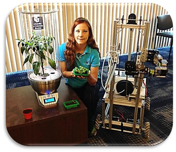 Heather Hava (CEO) with SmartPOT (SPOT) and Remotely Operated Gardening Rover (ROGR). Image Credit: Stellar Synergetics