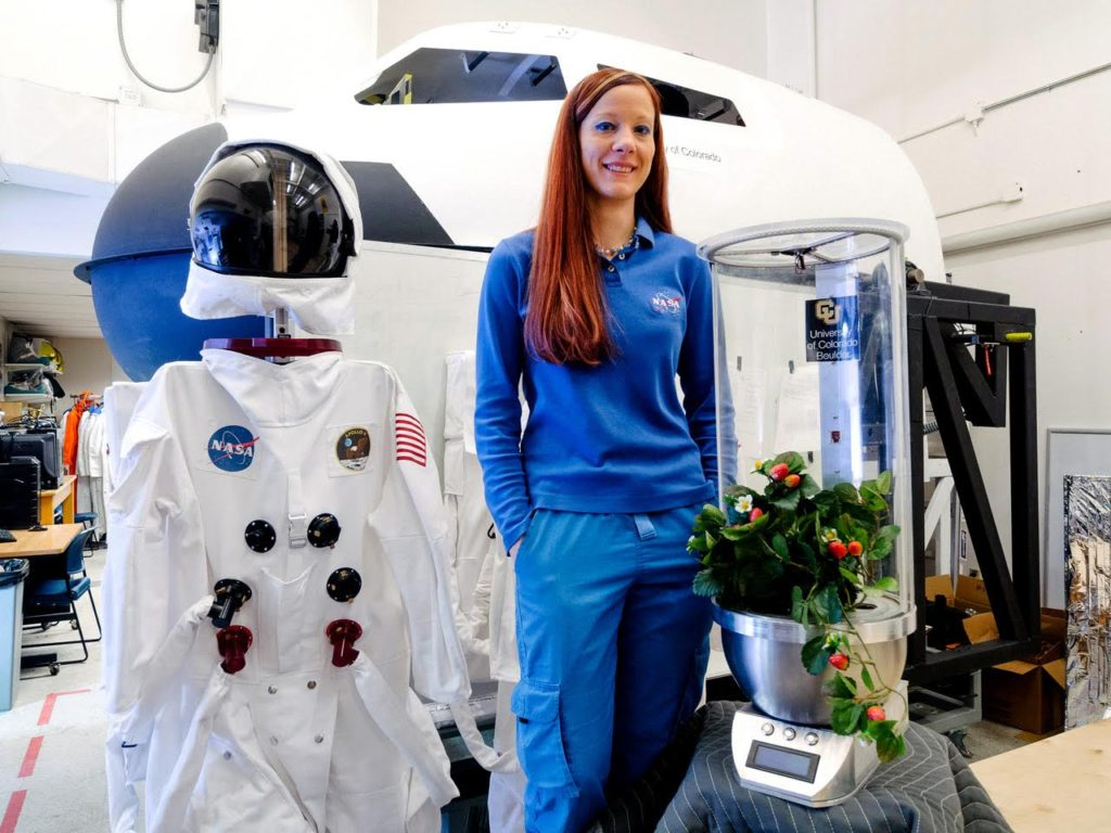 Heather Hava (CEO) with SmartPOT(SPOT) in front of the Dreamchaser at CU's Bio-Astronautics Lab. Image Credit: Stellar Synergetics