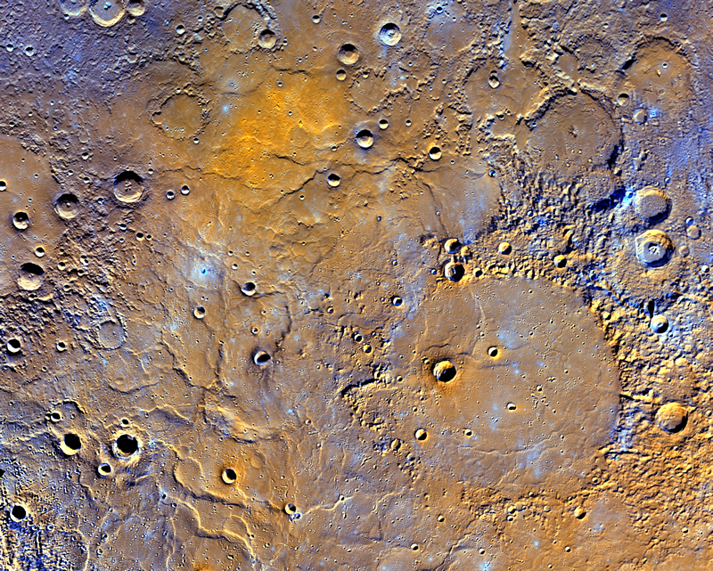A view of Mercury's northern volcanic plains from the new map released today, shown in enhanced color to emphasize different types of rocks on Mercury's surface. In the bottom right portion of the image, the 291-kilometer-diameter (181-mile-diameter) Mendelssohn impact basin, named after the German composer, may be seen to have been once nearly filled with lava. Toward the bottom left portion of the image, large wrinkle ridges, formed during lava cooling, are visible. Also in this region, the circular rims of impact craters buried by the lava can be identified. Near the top of the image, the bright orange region shows the location of a volcanic vent, newly identified because of this map and the source of one of the largest pyroclastic deposits on the planet. This view is shown in a polar stereographic map projection, and the north pole is toward the bottom left corner. Enhanced colors are created by placing the second principal component, the first principal component, and the ratio of images from the 430 nanometer and 1000 nanometer filters in the red, green, and blue channels, respectively. Image Credit: NASA/Johns Hopkins University Applied Physics Laboratory/Carnegie Institution of Washington
