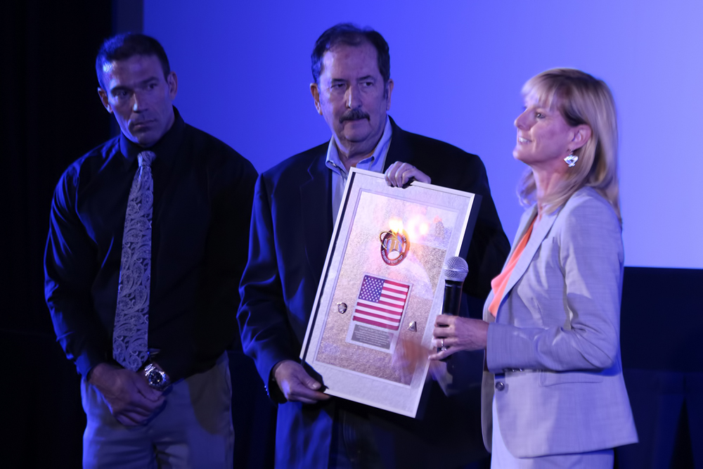 Kay Sears presents Littleton Mayor Bruce Beckman with a flag that was flown on Orion EFT-1 in December 2014. Image Credit: Colorado Space News
