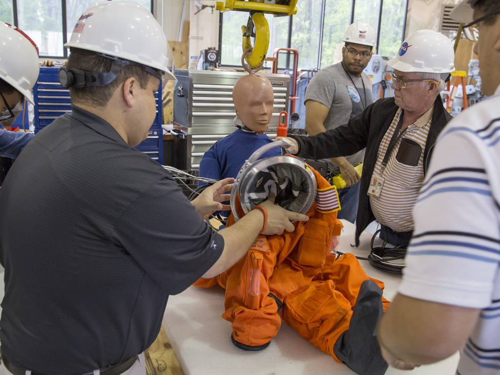 Engineers at NASA's Langley Research Center in Hampton, Virginia, dress a 105-pound representative female crash-test dummy into a modified Advanced Crew Escape System suit to prepare for water-impact testing at Langley's 20-foot-deep Hydro Impact Basin. Image Credit: NASA/David C. Bowman