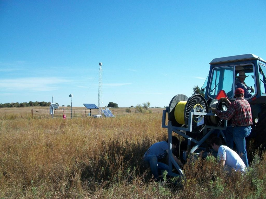 The Distributed Temperature Sensing system is being installed via a plowshear device on the back of a tractor. Graduate students are checking the insertion into the soil trench behind the tractor. Image Credit: M. H. Cosh.