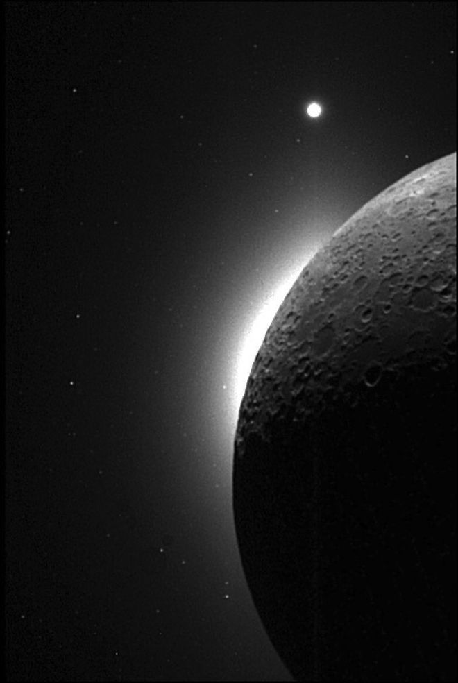 The slim, bright crescent, known as lunar horizon glow was witnessed several times during Apollo missions. This picture was taken with the Clementine spacecraft, when the sun was behind the moon. The white area on the edge of the moon is the LHG, and the bright dot at the top is the planet Venus. Image Credit: NASA