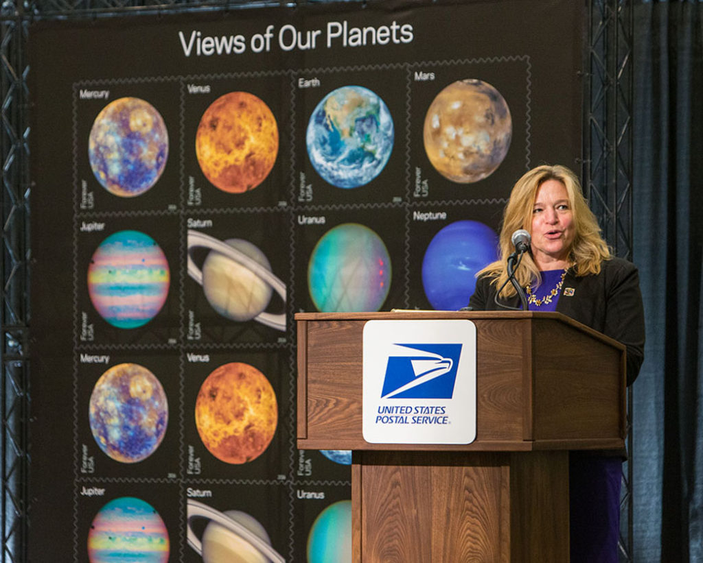 NASA Chief Scientist Ellen Stofan addresses a crowd of stamp aficionados at the World Stamp Show-NY 2016 at the Javits Center, New York. Image Credit: USPS/Daniel Afzal