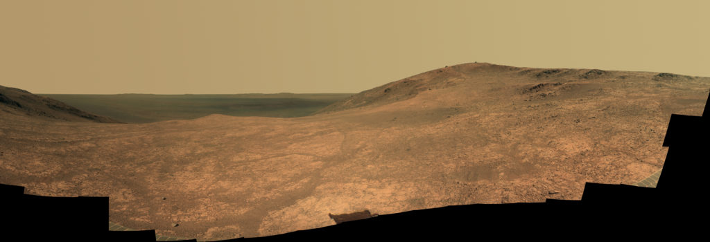 """Marathon Valley"" on Mars opens to a view across Endeavour Crater in this scene from the Pancam of NASA's Mars rover Opportunity. The scene merges many exposures taken during April and May 2016. The view spans from north (left) to west-southwest. Its foreground shows the valley's fractured texture. Image Credit: NASA/JPL-Caltech/Cornell Univ./Arizona State Univ."