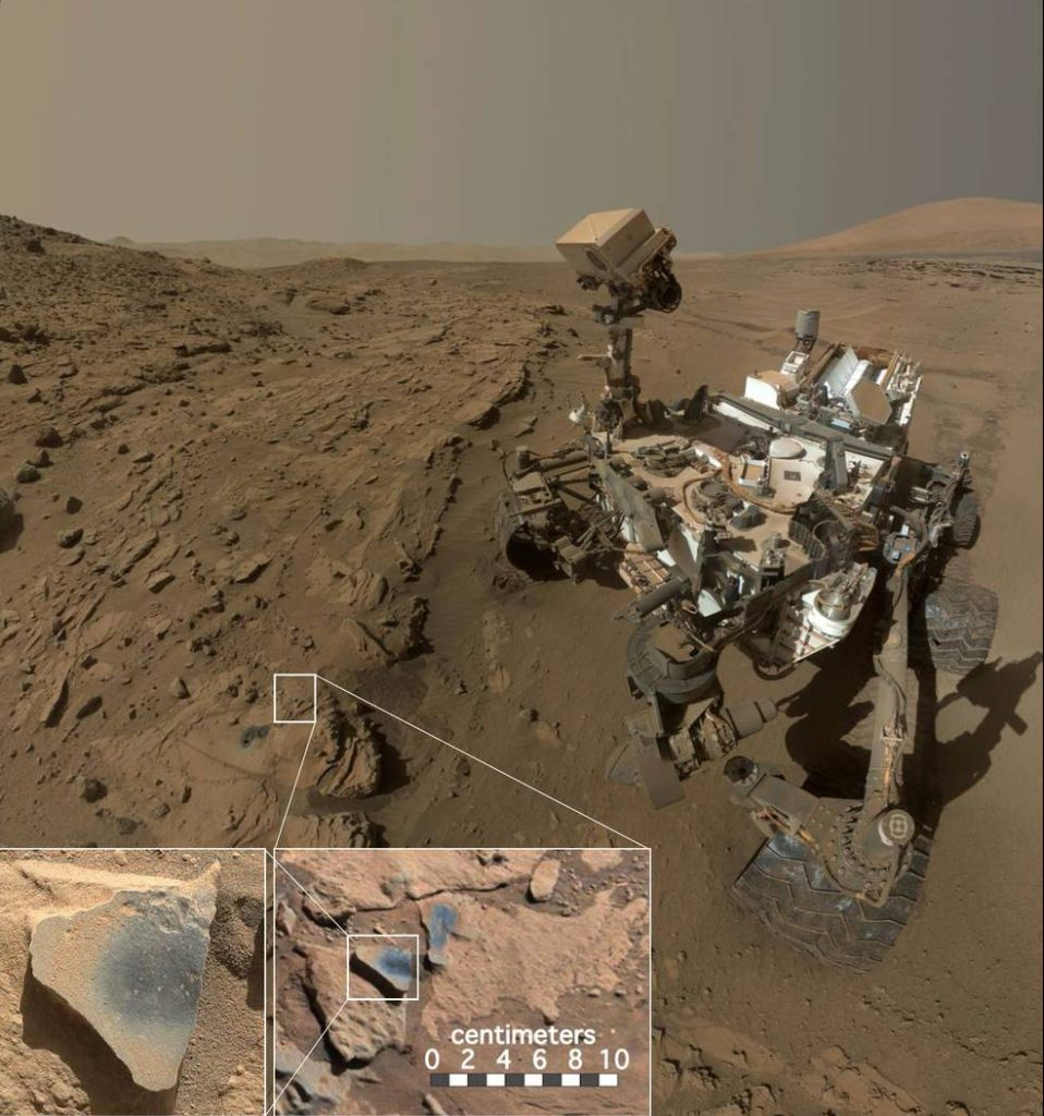 "This scene shows NASA's Curiosity Mars rover at a location called ""Windjana,"" where the rover found rocks containing manganese-oxide minerals, which require abundant water and strongly oxidizing conditions to form. In front of the rover are two holes from the rover's sample-collection drill and several dark-toned features that have been cleared of dust (see inset images). These flat features are erosion-resistant fracture fills containing manganese oxides. The discovery of these materials suggests the Martian atmosphere might once have contained higher abundances of free oxygen than it does now. Image Credit: NASA/JPL-Caltech/MSSS"