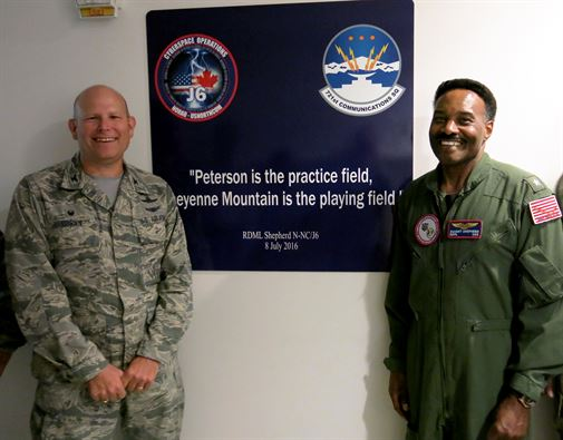 Rear Adm. Dwight Shepherd, North American Aerospace Defense and United States Northern Command cybersystems director, right, and Col. Gary Cornn, Cheyenne Mountain Air Force Station commander, present the newly unveiled sign honoring Shepherd's work related to network and software upgrades to the installation July 8, 2016. The quote was used to keep Shepehrd's team on track as the project is underway. Image Credit: USAF