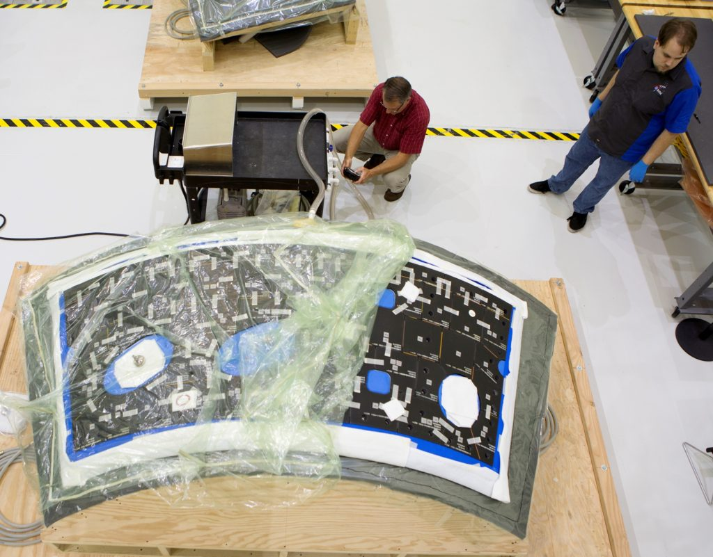 In the Neil Armstrong Operations and Checkout Building at NASA's Kennedy Space Center, technicians have begun bonding thermal protection system tiles to the nine panels the will cover the Orion crew module for the agency's first unpiloted flight test with the Space Launch System (SLS) on the agency's Journey to Mars. Image Credit: NASA/Cory Huston