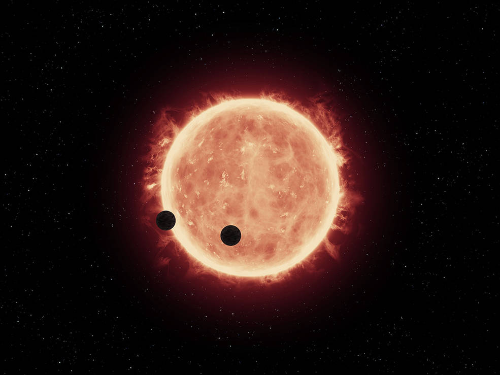 This artist's illustration shows two Earth-sized planets, TRAPPIST-1b and TRAPPIST-1c, passing in front of their parent red dwarf star, which is much smaller and cooler than our sun. NASA's Hubble Space Telescope looked for signs of atmospheres around these planets. Image Credit: NASA/ESA/STScI/J. de Wit (MIT)