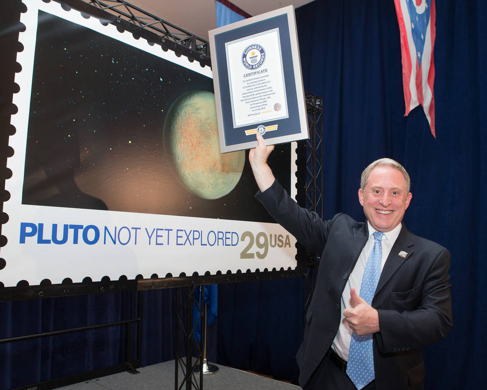 New Horizons Principal Investigator Alan Stern celebrates a Guinness World Record certificate on July 19 at U.S. Postal Service Headquarters in Washington, D.C. Image Credit: Dan Afzal, U.S. Postal Service