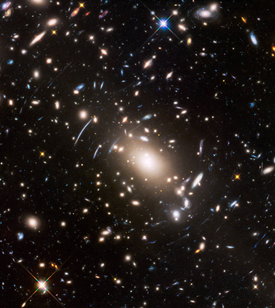"This view of a massive cluster of galaxies unveils a very cluttered-looking universe filled with galaxies near and far. Some are distorted like a funhouse mirror through a ""space warp"" phenomenon first predicted by Einstein a century ago. Image Credit: NASA, ESA, and J. Lotz (STScI)"