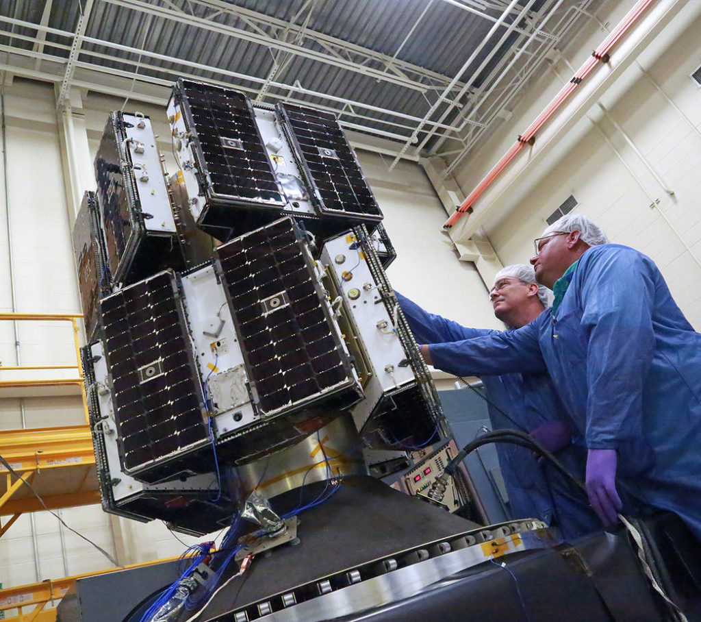 Engineers prepare NASA's eight Cyclone Global Navigation Satellite System (CYGNSS) microsatellites, mounted on the deployment module, for vibration testing at the Southwest Research Institute in San Antonio, Texas. Image Credit: Southwest Research Institute