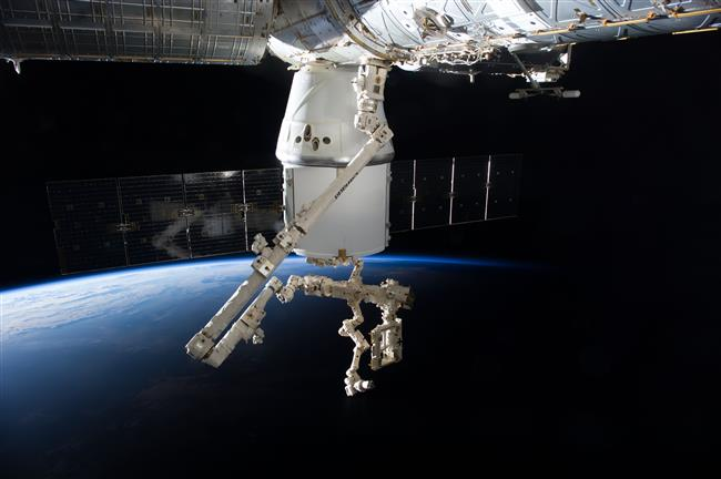 An ISS crew member captured this view of Dextre at the end of Canadarm2, prepared to remove cargo from Dragon. Image Credit: NASA