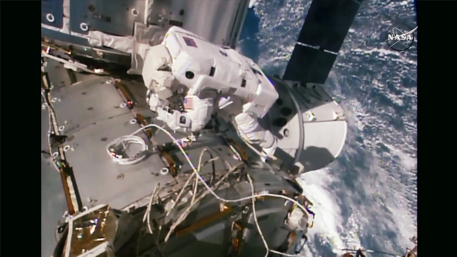 Spacewalker Kate Rubins works outside the International Space Station with the SpaceX Dragon space freighter just below her. Image Credit: NASA TV