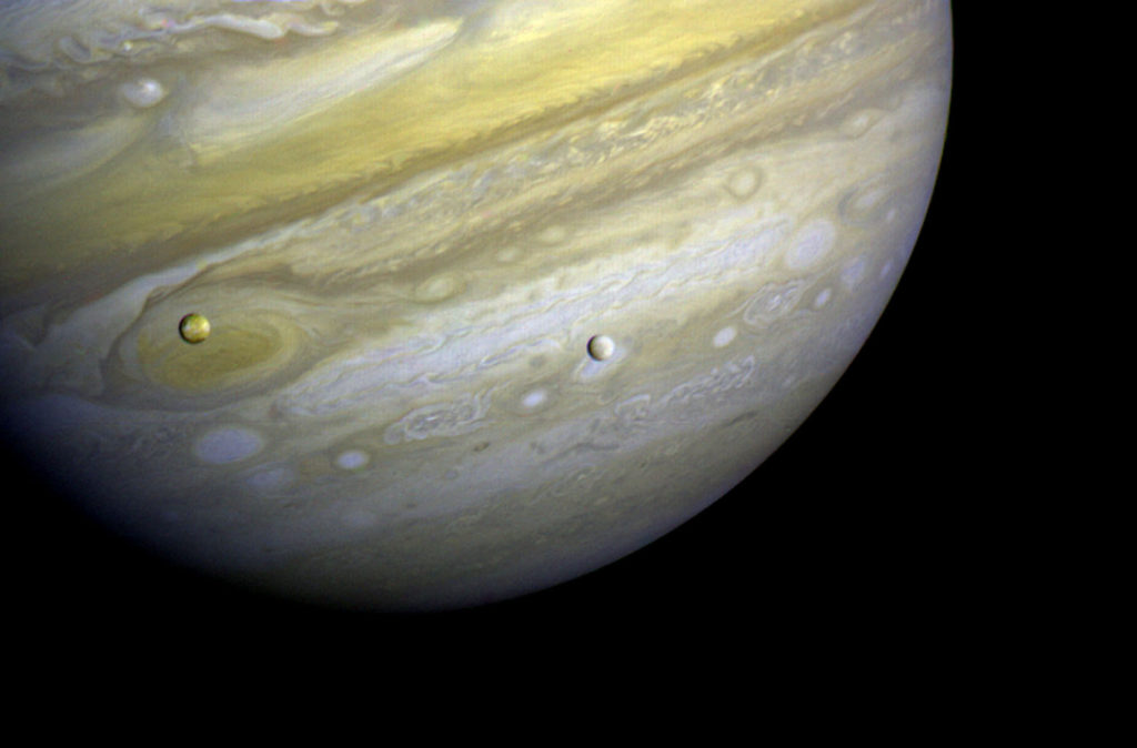 Voyager 1 took this photo of Jupiter and two of its satellites (Io, left, and Europa) on Feb. 13, 1979. This photo was assembled from three black and white negatives by the Image Processing Lab at Jet Propulsion Laboratory. Image Credit: NASA/JPL
