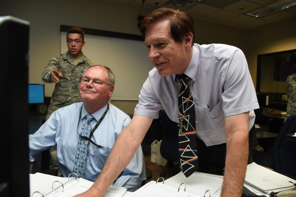 Bruce Carlson (center), Boeing technical advisor, and Mike O'Brine (right), Aerospace Corporation, send the final command to dispose of Global Positioning System Satellite Vehicle Number 23 at Schriever Air Force Base, Colorado, Friday, Aug. 26, 2016. Both of them were on the operations floor November 1990, when the satellite initially launched and when the solar array stopped working. They, along with the operators working, saved the satellite by tweaking its operating mode, and extended its life to 25 years. Image Credit: U.S. Air Force/2nd Lt. Darren Domingo